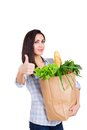 Happy young woman holding paper bag with groceries Royalty Free Stock Photo