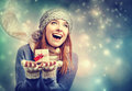 Happy young woman holding a small present box in snowy night Royalty Free Stock Photo