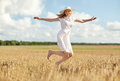 Happy young woman jumping on cereal field Royalty Free Stock Photo