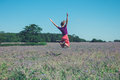 Happy young woman jumping in field of purple flowers Royalty Free Stock Photo
