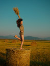 Happy, young woman jumping on hay stack Royalty Free Stock Photo