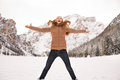 Happy young woman jumping outdoors among snow-capped mountains Royalty Free Stock Photo