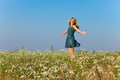The happy young woman jumps in the field of camomiles portrait in a sunny day Royalty Free Stock Photography