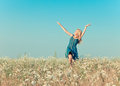 The happy young woman jumps in the field of camomiles with a retro effect Stock Image