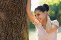 Happy young woman lean against tree Royalty Free Stock Image