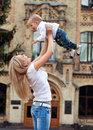 Happy young woman lifting her son high up Stock Photos