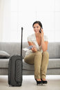 Happy young woman living room travel bag talking mobile phone Royalty Free Stock Photo