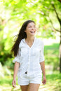 Happy young woman looking away in park she is casuals mixed race asian caucasian female is walking Stock Image