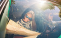 Happy young woman looking a map inside of car portrait women with sunglasses while her friend driving in road trip adventure Royalty Free Stock Image