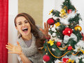 Happy young woman looking out from christmas tree high resolution photo Royalty Free Stock Photos
