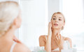 Happy young woman looking to mirror at bathroom Royalty Free Stock Photo