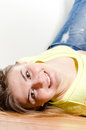 Happy young woman lying on floor and smiling joyfully looking in camera Royalty Free Stock Image
