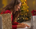 Happy young woman making christmas list of presents in decorated kitchen Royalty Free Stock Photography
