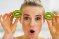 Happy young woman making eyes with kiwi slices in kitchen Royalty Free Stock Photos