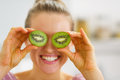 Happy young woman making eyes with kiwi slices in kitchen Stock Image