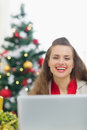 Happy young woman near Christmas tree with laptop Stock Photo