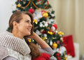Happy young woman near christmas tree looking on copy space high resolution photo Royalty Free Stock Photo