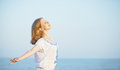 Happy young woman open her arms to the sky and sea Royalty Free Stock Photo