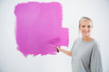 Happy young woman painting her wall pink and smiling at camera Royalty Free Stock Images