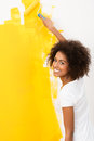 Happy young woman painting a wall orange african american with cute curly afro hairstyle with roller as she does home Stock Photos