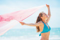 Happy young woman with parero rejoicing on beach in swimsuit Stock Photos
