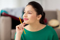 Happy young woman with pencil thinking Royalty Free Stock Photo