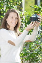 Happy young woman photographer using old camera fashioned taking pictures Royalty Free Stock Images