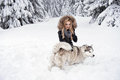 Happy young woman playing with dogs siberian husky in winter forest Royalty Free Stock Photography
