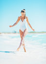 Happy young woman playing with water on beach in white swimsuit Royalty Free Stock Photos