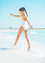 Happy young woman playing with waves on beach in white swimsuit Stock Photo