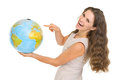 Happy young woman pointing on globe Stock Photo