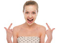 Happy young woman pointing on oatmeal mask isolated white Stock Images