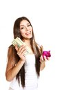 Happy young woman posing with a piggy bank and dollars on a whit white background Royalty Free Stock Photos