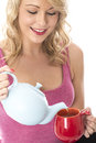 Happy Young Woman Pouring Tea from a Teapot Into Red Mug Royalty Free Stock Photo