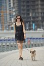 Happy young woman with puppy have fun beautiful in black dress cute small dog on street Royalty Free Stock Images
