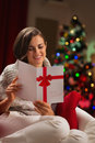 Happy young woman reading Christmas postcard Royalty Free Stock Image