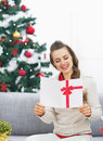 Happy young woman reading christmas postcard near christmas tree high resolution photo Royalty Free Stock Photo