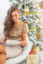 Happy young woman reading magazine near christmas tree in living room Stock Photos