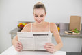 Happy young woman reading a newspaper in the kitchen at home Stock Photography