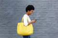 Happy young woman reading text message on mobile phone side portrait of a with a bag her Stock Image