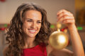 Happy young woman in red dress holding christmas ball kitchen Stock Photo