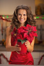 Happy young woman in red dress holding christmas rose in kitchen decorated Royalty Free Stock Photos