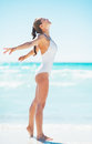 Happy young woman rejoicing on beach in white swimsuit Stock Image