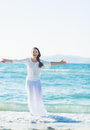 Happy young woman rejoicing on sea shore high resolution photo Royalty Free Stock Photography
