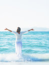 Happy young woman rejoicing on sea shore rear view high resolution photo Stock Photo