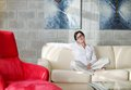 Happy young woman relax at home on sofa in bright living room and watching tv Royalty Free Stock Photography