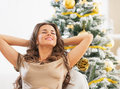 Happy young woman relaxing in front of christmas tree portrait Stock Photography