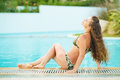 Happy young woman relaxing at poolside in swimsuit Royalty Free Stock Photography
