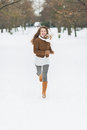 Happy young woman running in winter park with long hair Royalty Free Stock Images