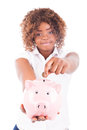 Happy young woman saves money in piggy bank isolated Royalty Free Stock Photos